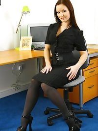 The lovely Jana B in a dark office outift and thick grey..