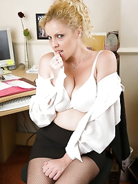 Blonde Taya shows off her massive breasts in these office..