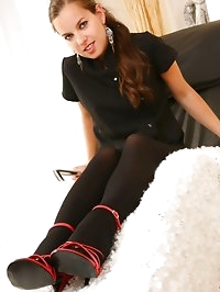 Cute brunette wearing black minidress, stockings and red..