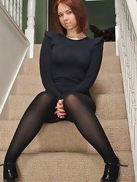 Ellie Rose in a black dress, pantyhose and high heels..