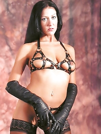 Sultry looking Mistress in leather gloves and a leather..