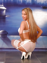 Busty blonde in sheer white lingerie & stockings with..