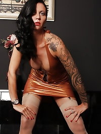 Tattooed Sofia dressed in gold latex dress with stockings..